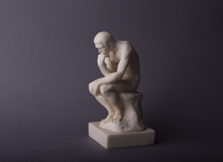 A small statue of a man sitting with his head resting on his hand, thinking. It symbolises considering digital ethics.