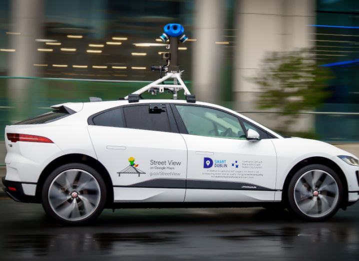 A white Google Street View car equipped with tech devices on its roof is driving down a Dublin street.