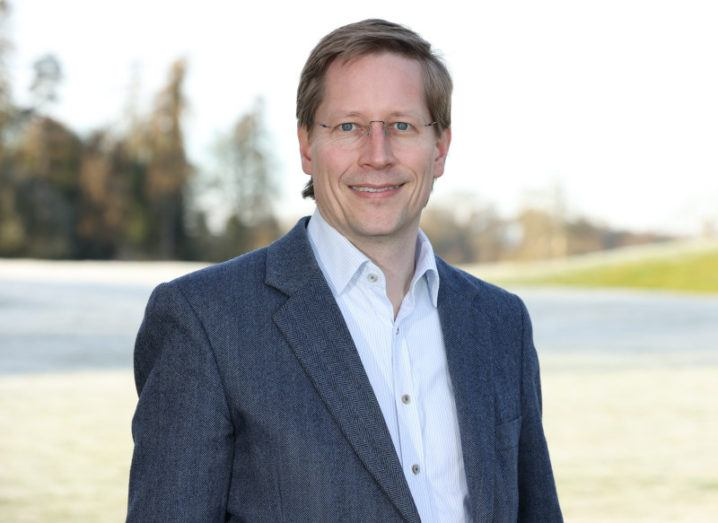Holger Claussen wears a blue-grey twill blazer and white shirt. He is pictured outdoors, with a blurred green landscape in the background.