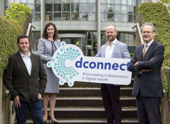 Four people stand on the steps of a DkIT building, holding a sign that says 'dConnect'.