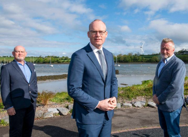 Three men in suits stand outside on a sunny day in front of a harbour with a wind turbine in the background.