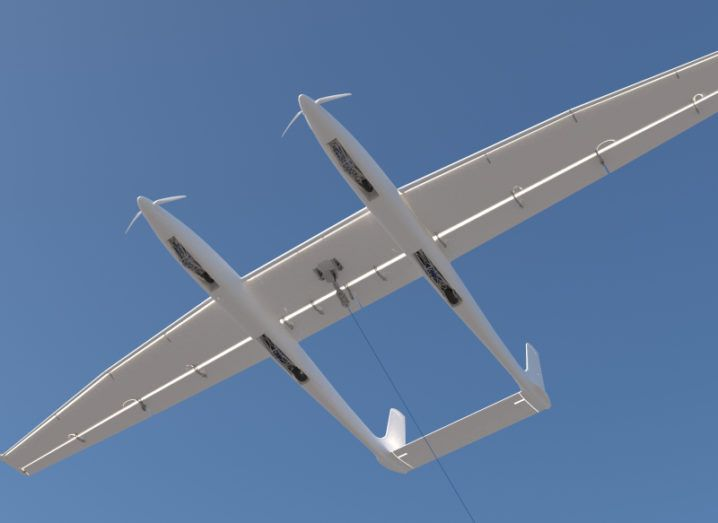 Image of a small white aircraft-like device flying against a bright blue sky.