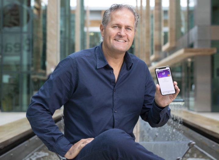 CleverCards founder and CEO Kealan Lennon is sitting outdoors in a modern business district and smiling into the camera. He is holding up a phone with the CleverCards app open.