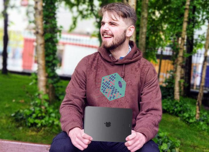 A man is sitting outdoors on a wall holding a tablet computer,