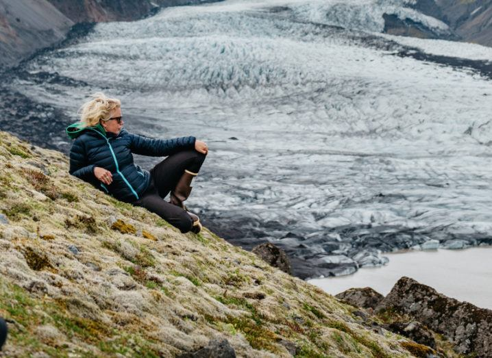 Glaciologist M Jackson sits on a mossy hill looking out at a glacier.