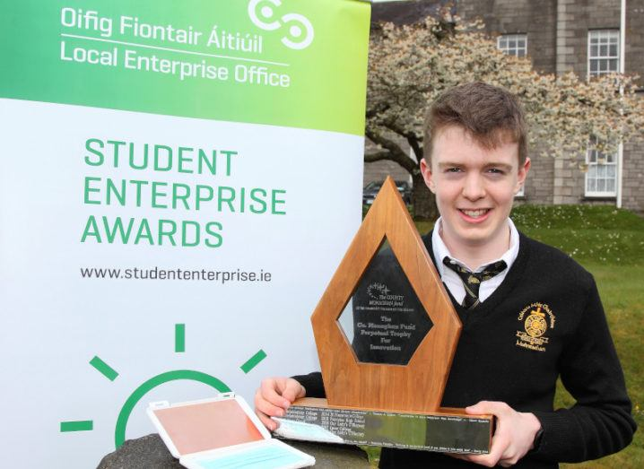 Student Matthew McVicar holds a large wooden award, while standing beside his CopperCase invention in front of a sign that reads 'Student Enterprise Awards'.