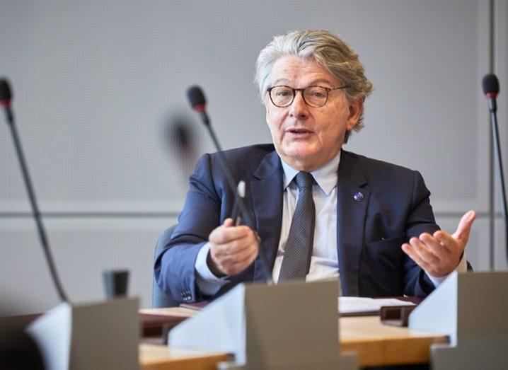Thierry Breton is sitting at a conference table in front of a microphone.