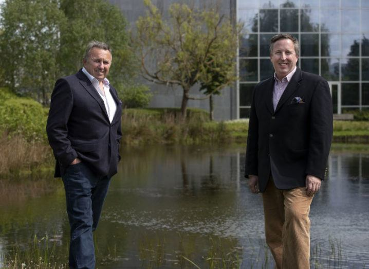 Two businessmen stand by a pond in front of a large glass-walled building.