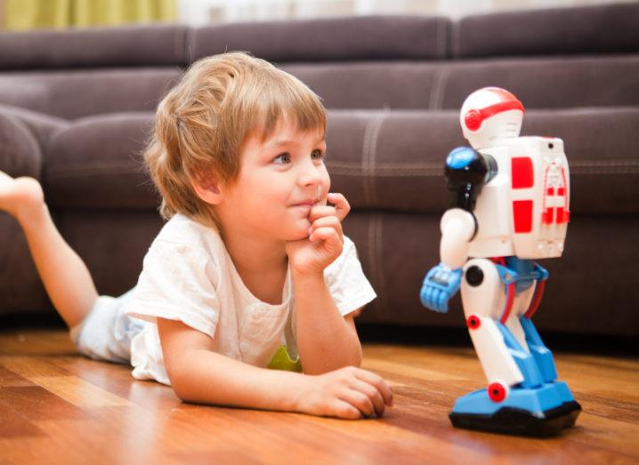 A little boy lying on a wooden floor, playing with robot toy.