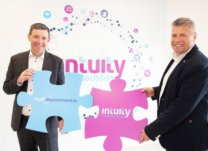 Two men stand in front of a wall that has the Intuity Technology logo on it. They are each holding a large puzzle piece, one with the Intuity logo and the other with the MyITDepartment logo.