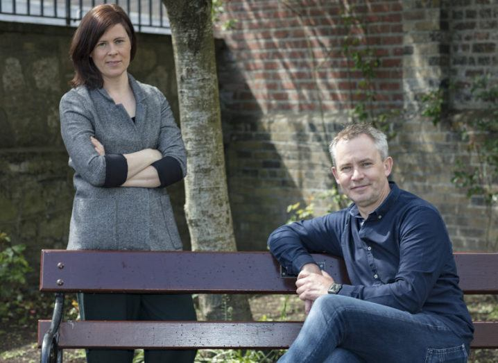 Patricia Scanlon stands with her arms folded behind a bench on which Martyn Farrows is seated.
