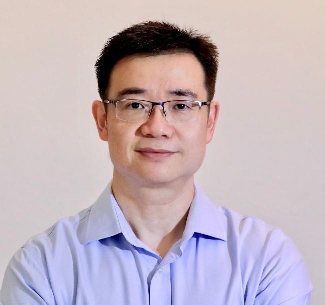 Un homme à lunettes portant une chemise bleu clair sourit à la caméra.