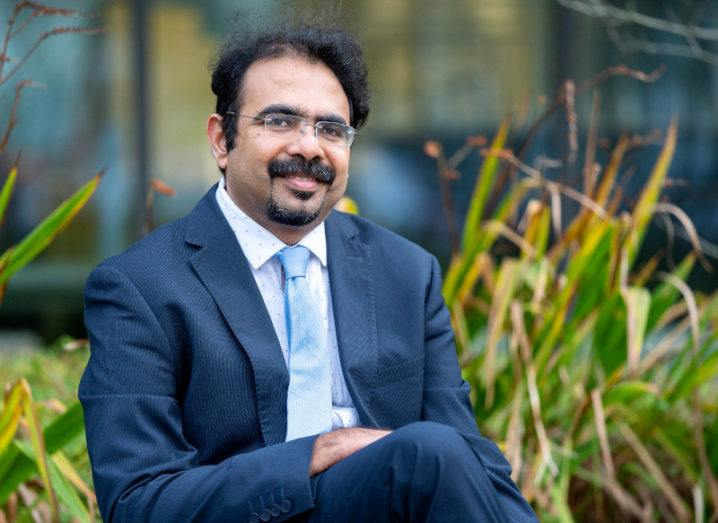 Prof Suresh C Pillai sits outdoors among some greenery. He's wearing a suit and smiling at the camera.