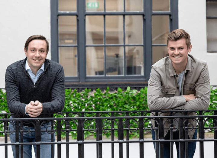 Two men stand outside, leaning on a black railing in front of them, smiling at the camera. They are the founders of Wayflyer.