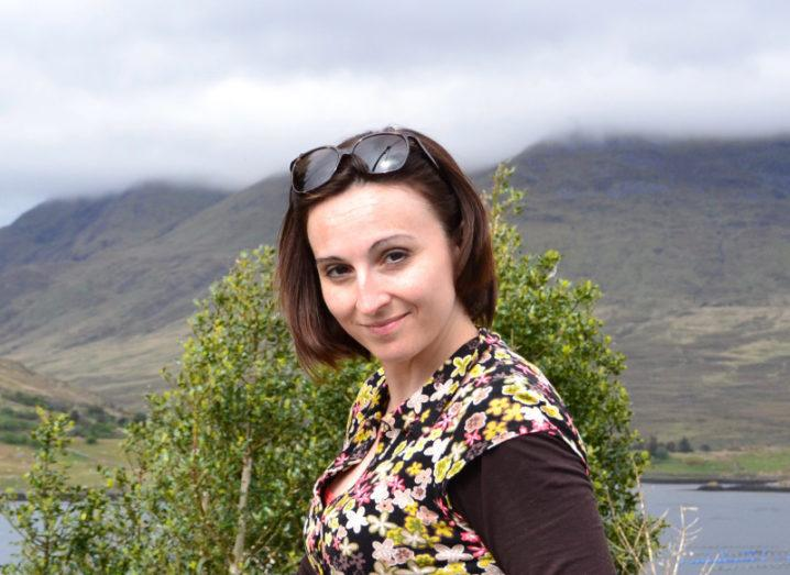 A woman in a floral top with sunglasses pushed to the top of her head is pictured in front of a mountainous landscape on a cloudy day.