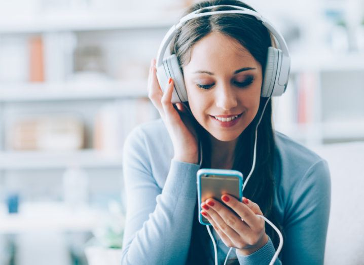 A young woman listening to music through white headphones that are plugged into the smartphone that she's looking at.