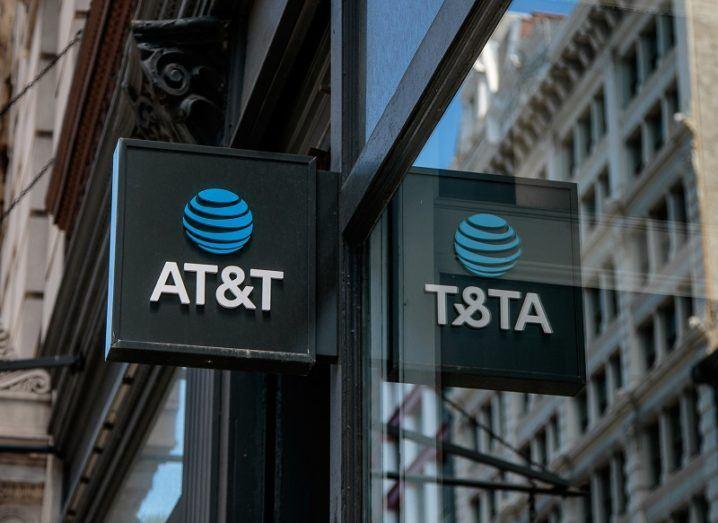 An AT&T sign is on the side of a building on a city street.