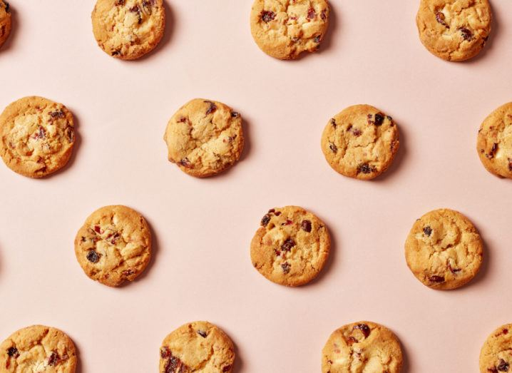 Chocolate chip cookies evenly spaced out on a pale pink background, symbolising third-party cookies.