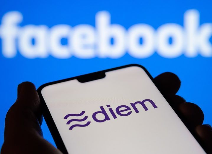 Diem currency logo visible on a smartphone silhouetted against a blurred Facebook logo.