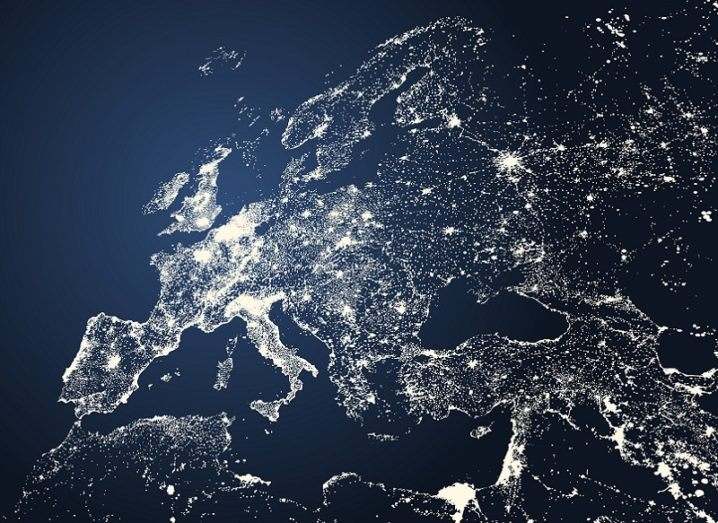 An illustrated map of Europe with bright lights emerging from cities and other populated regions.