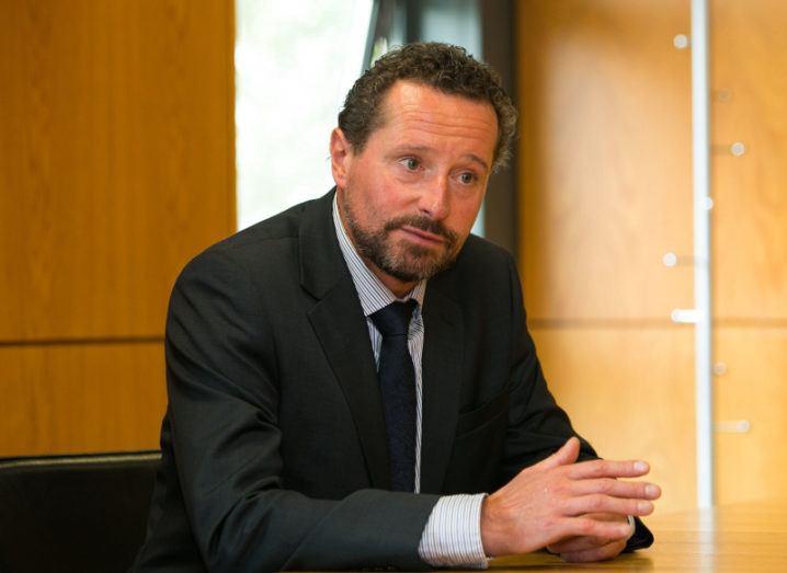 Gavin Walker sits in a suit in an office room.