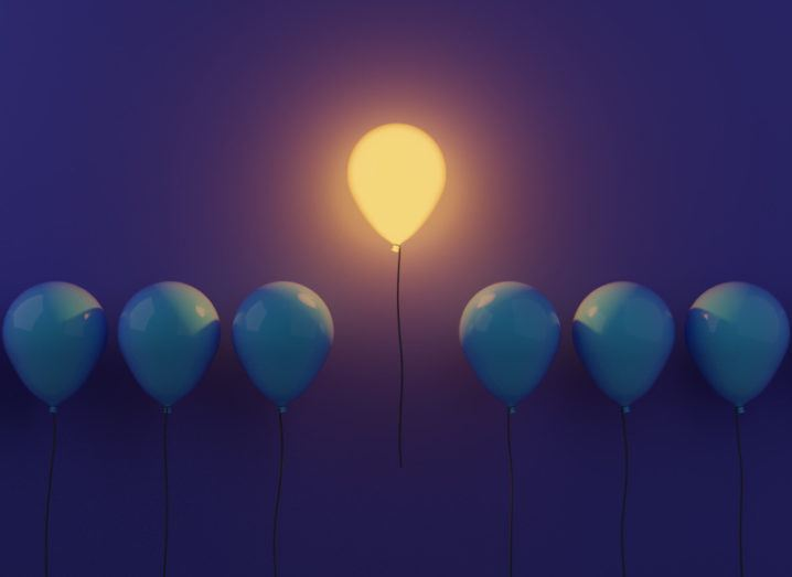 A glowing yellow balloon floats higher than a line of dark blue balloons against a purple background.