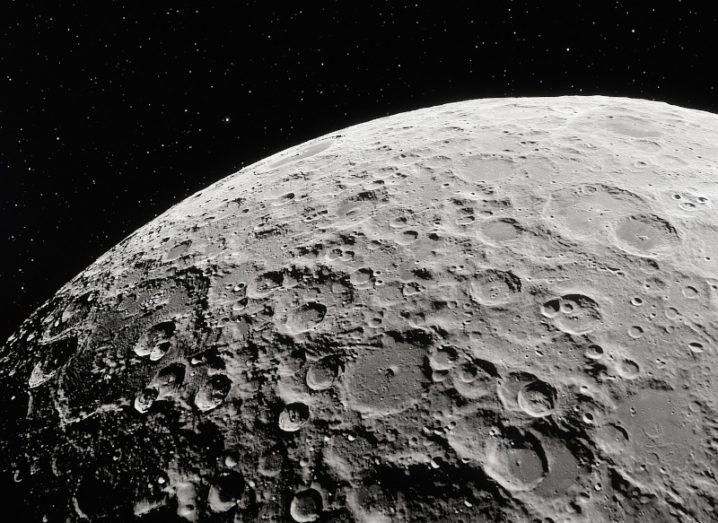A close-up of the surface of the moon against the background of space and stars.