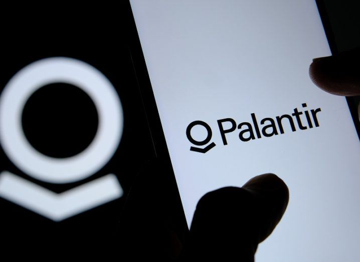 Silhouette of fingers on a smartphone, which has the Palantir logo on the screen.