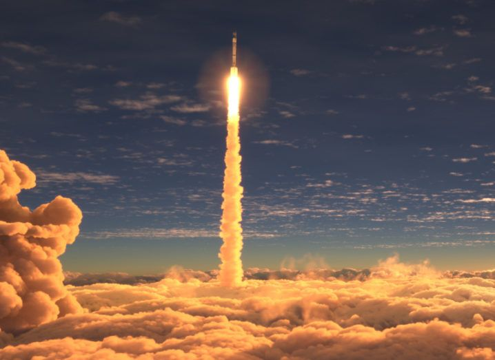 A rocket flies upwards through the sky at sunset. There's a bed of clouds at the bottom of the picture.