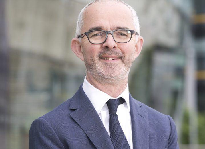 Stuart Harvey stands outdoors in a suit.