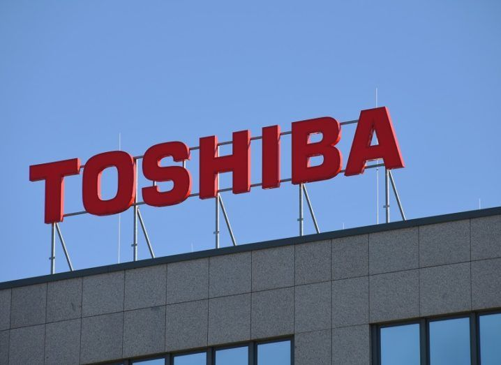A Toshiba office building in Germany. The Toshiba brand is on a structure across the roof of the building, backed by a clear blue sky.