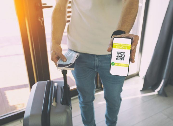 A man with a suitcase is showing a digital health passport app on his smartphone.