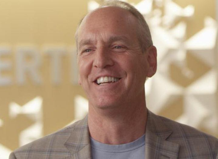 A man in a blazer and T-shirt in neutral tones smiles against a backdrop featuring a blurred Vertex logo.