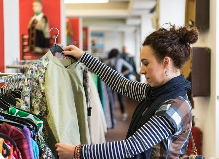 Woman browsing through vintage thrift store clothing.