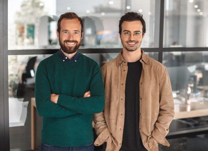 Thibault Chassagne and Karim Kaddoura stand in casual clothes in a bright office space.
