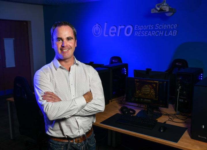 A man in a polkadot shirt stands in a darkened computer lab with Lero Esports Science Research Lab lit up in blue on the back wall.