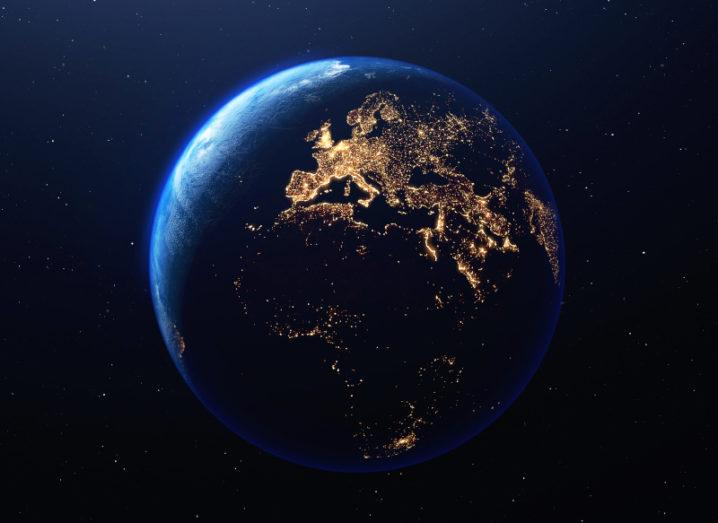 A three-dimensional render of the planet Earth from space. Europe is lit up by lights, which are glowing yellow against the blue of Earth. Stars glow faintly in the background in the darkness of space.