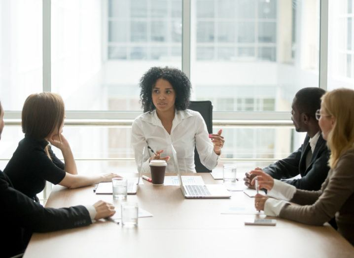 A woman sits at the top of a boardroom table speaking to colleagues in a bright room.