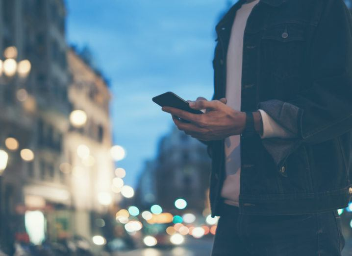 A man is using his smartphone on a city street at night.