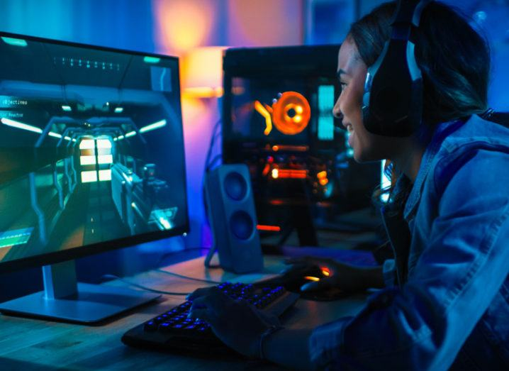 A young woman in a denim jacket plays a video game on a desktop computer with a light-up keyboard and wireless headphones. She is smiling, wholly immersed in the game.
