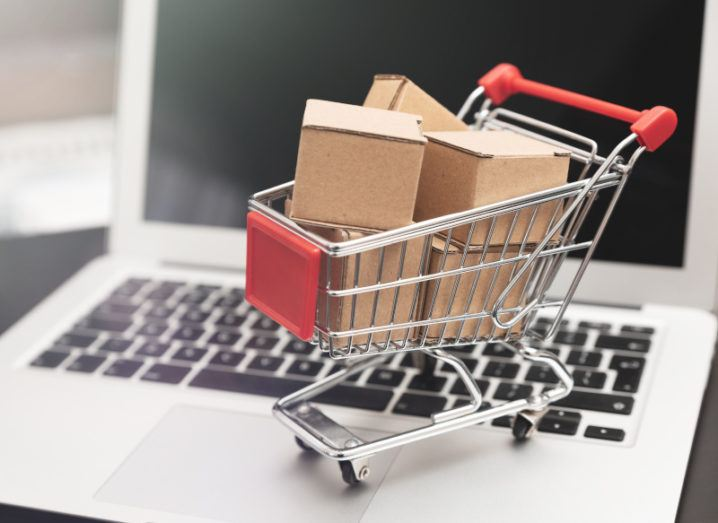 A miniature shopping cart filled with cardboard boxes is sitting on a laptop's keyboard.