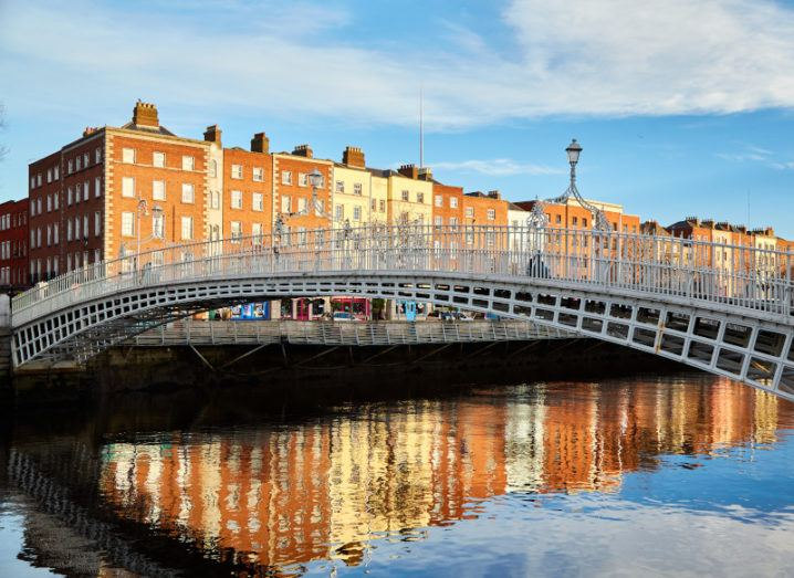 The Ha'penny Bridge crossing the river in Dublin city centre, with old brick buildings in the background.