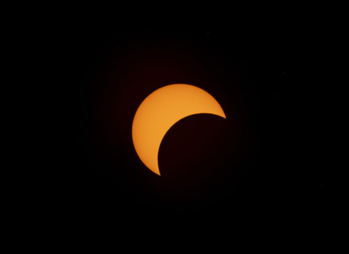 The sun against a dark sky with a semicircle covered on the side.
