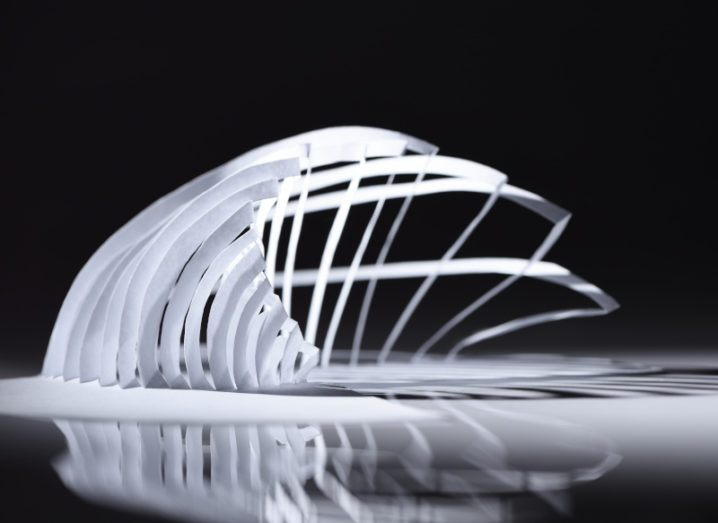 A sheet of white paper cut and folded to make a three-dimensional shape made up of curved paper strips.