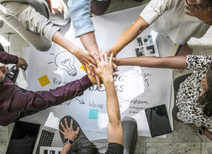 Six employees placing their hands on top of one another in a gesture synonymous with teamwork.