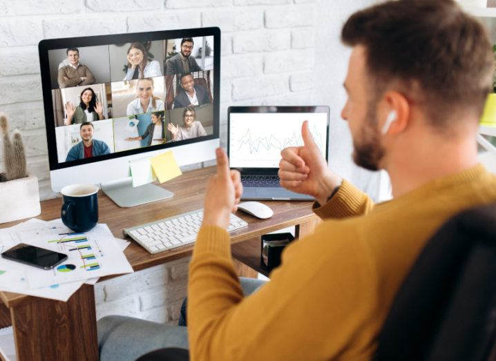A man gives two thumbs up to his colleagues on a Zoom call. Their faces appear in a grid on his Mac computer in his home office.