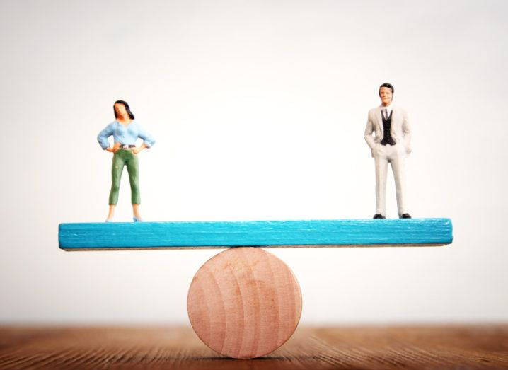 Miniature figurines representing a man and a woman are balanced on either end of a see-saw.