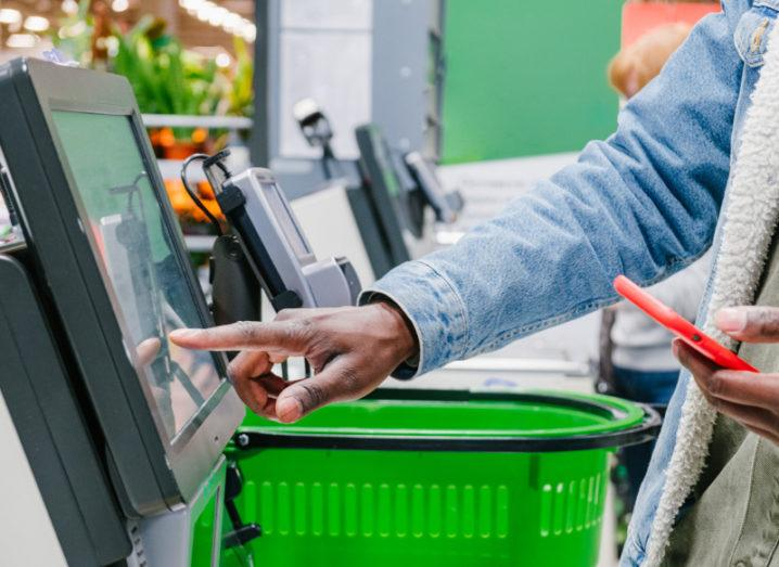 A man holding a phone touches the screen at a self-service checkout in a supermarket.
