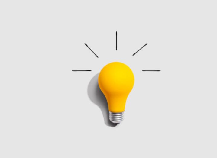 A bright yellow lightbulb is sitting against a grey background, with five lines emerging from the top of it.