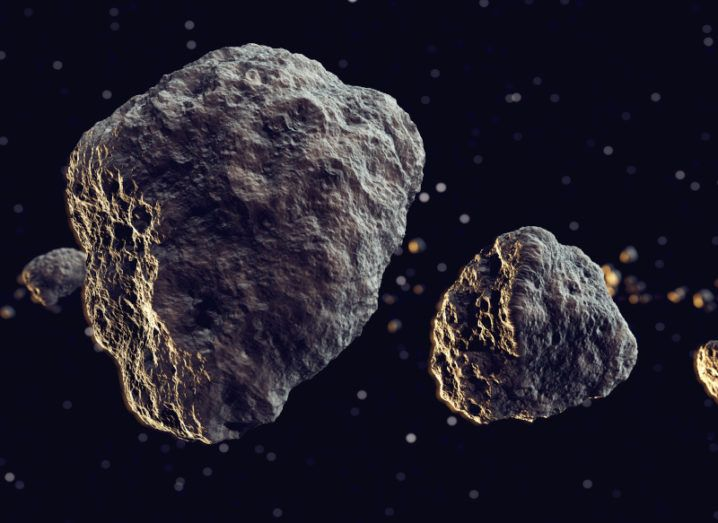 Two asteroids are depicted in space. The larger asteroid is on the left, with its smaller companion on the right. There are more asteroids floating in the background.